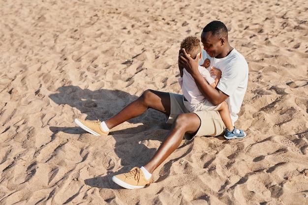ビーチtogeで砂の上に座っている間息子を保持している若いアフリカ系アメリカ人の父の完全な長さの肖像画...