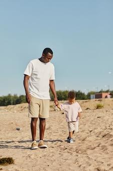 カメラに向かって歩いているビーチで赤ちゃんの息子と若いアフリカ系アメリカ人の父の完全な長さの肖像画...