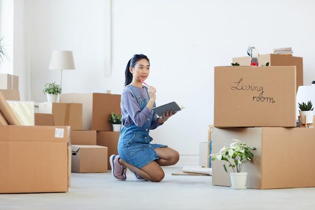 Портрет молодой азиатской женщины в полный рост, занимающейся организацией переезда, сидя на полу рядом с картонными коробками и держа в руках планировщик