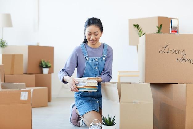 Портрет молодой азиатской женщины в полный рост, упаковывающей книги в картонные коробки и счастливо улыбающейся, взволнованной перед переездом в новый дом или общежитие