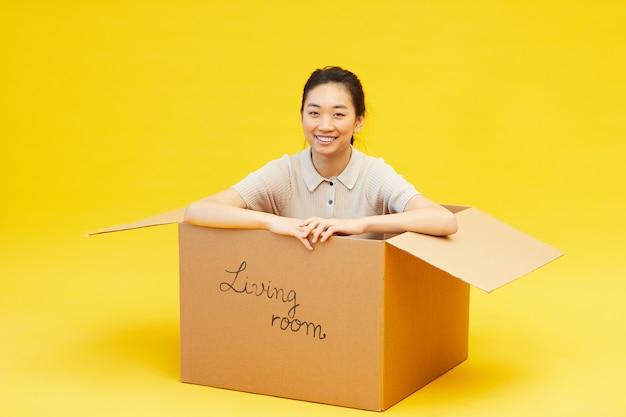 상자에 앉아 웃 고 젊은 아시아 여자의 전체 길이 초상화