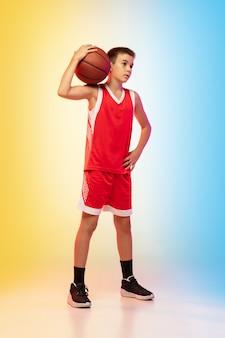 Полнометражный портрет молодого баскетболиста в униформе на фоне студии градиента. подросток уверенно позирует с мячом. понятие спорта, движения, здорового образа жизни, рекламы, действий, движения.