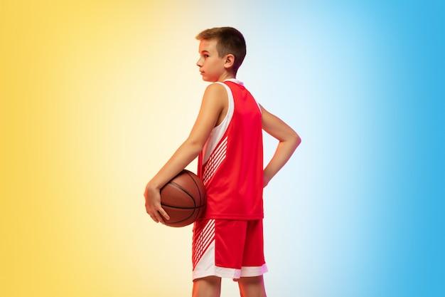 Полнометражный портрет молодого баскетболиста в униформе на фоне студии градиента. подросток уверенно тренируется с мячом. понятие спорта, движения, здорового образа жизни, рекламы, действий, движения.