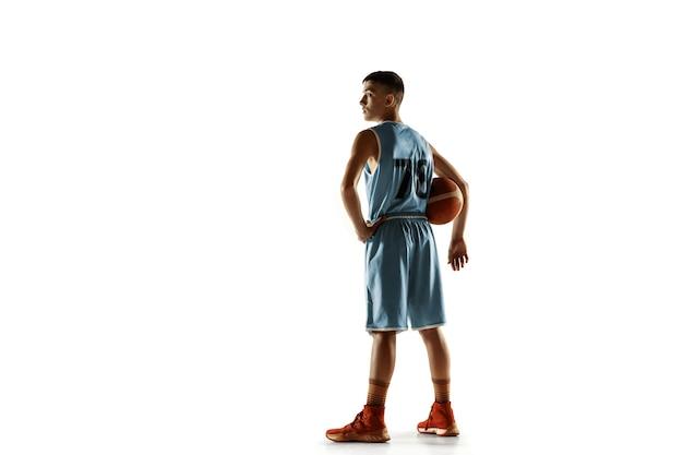 白いスペースで隔離のボールを持つ若いバスケットボール選手の全身像
