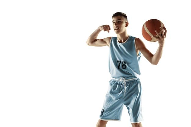 白いスタジオの背景に分離されたボールを持つ若いバスケットボール選手の全身像。勝利を祝うティーンエイジャー。スポーツ、動き、健康的なライフスタイル、広告、アクション、モーションの概念。