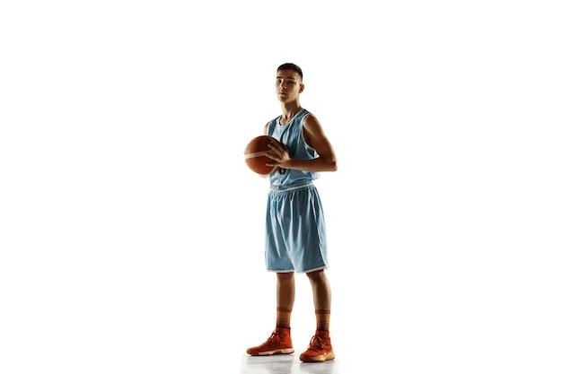 白いスタジオの背景に分離されたボールを持つ若いバスケットボール選手の全身像。ボールでポーズをとることに自信を持っているティーンエイジャー。スポーツ、動き、健康的なライフスタイル、広告、アクション、モーションの概念。