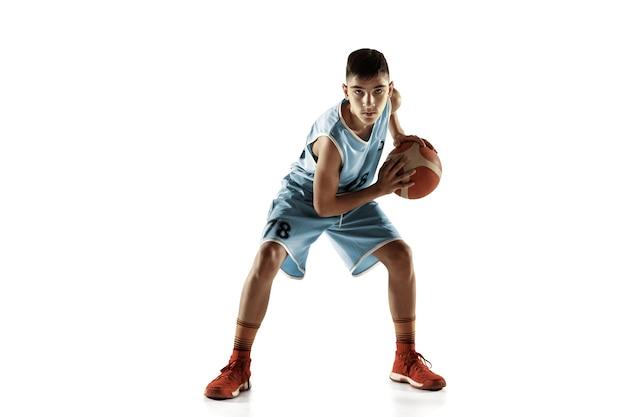 白いスタジオの背景に分離されたボールを持つ若いバスケットボール選手の全身像。 10代の若者のトレーニングと練習、アクション、モーション。スポーツ、動き、健康的なライフスタイル、広告の概念。