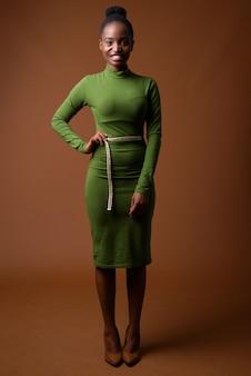 Полнометражный портрет молодой красивой деловой женщины африканских зулусов улыбается