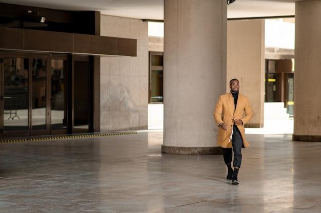 Полнометражный портрет молодого черного бизнесмена, идущего по городу.