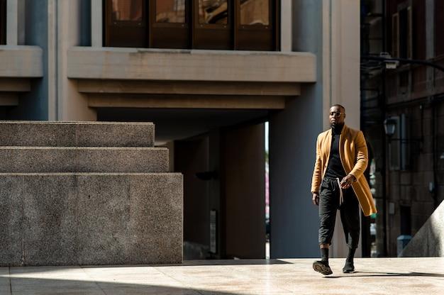 Полнометражный портрет молодого чернокожего человека, идущего по городу в модном костюме.