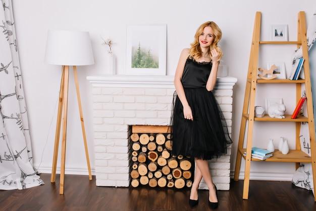 素敵でモダンなインテリア、床ランプ、偽の暖炉、人形、本が付いている棚の明るい部屋で若いブロンドの女性の完全な長さの肖像画。スタイリッシュな黒のドレスと靴を履いています。