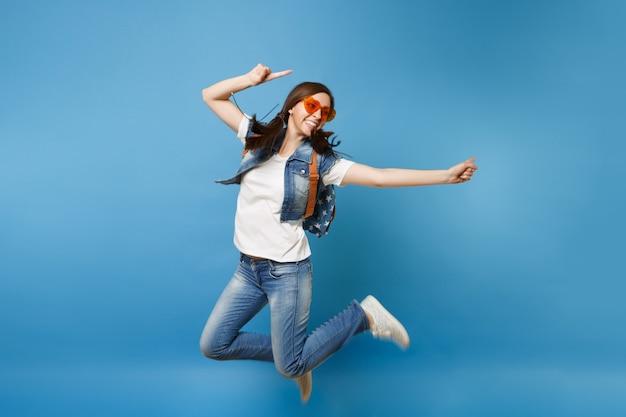 Полнометражный портрет молодого жизнерадостного студента женщины в оранжевых очках сердца скача указывая указательные пальцы в сторону, изолированные на синем фоне. обучение в средней школе. скопируйте место для рекламы.