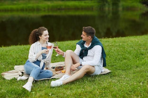 緑の芝生に座ってワインを飲みながら湖のほとりでロマンチックなデートを楽しんでいる若いカップルの全身像