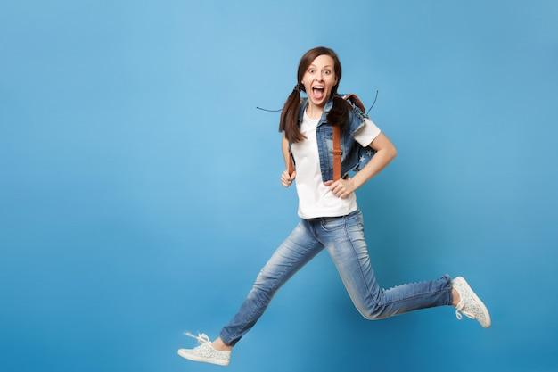 Полнометражный портрет молодого возбужденного жизнерадостного студента женщины с открытым ртом с рюкзаком, прыгающим, раздвигая ноги, изолированные на синем фоне. обучение в университете. скопируйте место для рекламы.