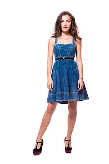 흰색 배경에 고립 된 허리에 그녀의 손으로 서 파란 드레스에 젊은 여성의 전체 길이 초상화