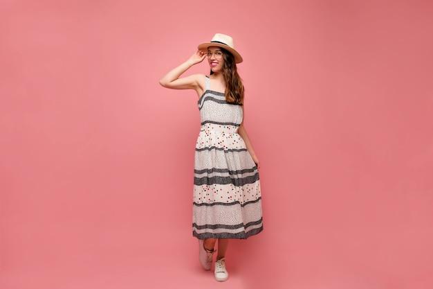 幸せな笑顔でスタジオで踊る流行のドレスの若い女性モデルの全身像