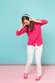 バラのシャツのブラウス、白いズボン、明るいピンクブルーのパステルカラーの壁に分離されたヘッドフォンダンスの若い楽しい女性の完全な長さの肖像画。