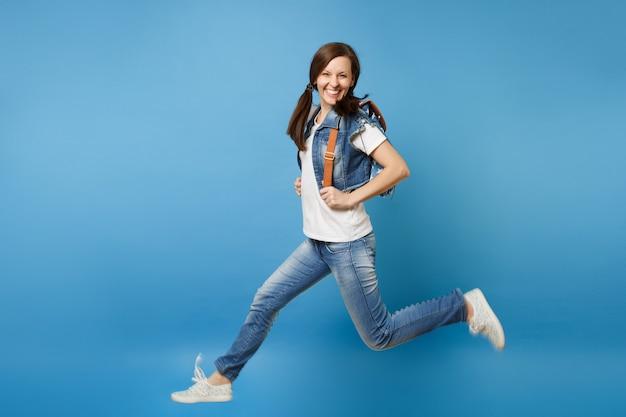 Полнометражный портрет молодого смешного симпатичного усмехаясь студента женщины в джинсовой одежде с рюкзаком, прыгающим, распространяя ноги, изолированные на синем фоне. обучение в колледже. скопируйте место для рекламы.