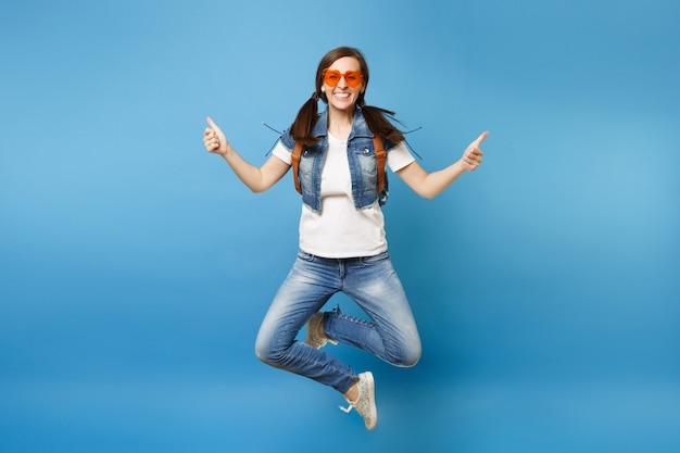 Полнометражный портрет молодой смешной студентки женщины в оранжевых очках сердца прыгают со скрещенными ногами, показывая большие пальцы руки вверх, изолированные на синем фоне. обучение в университете. скопируйте место для рекламы.