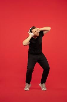 빨간 벽에 고립 된 젊은 높은 점프 남자의 전체 길이 초상화. 남성 백인 모델. copyspace. 인간의 감정, 표정, 스포츠 개념.
