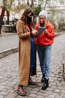 通りに立っている間デジタルタブレットを保持している暖かい服を着た若い女性の全身像。検疫中に医療保護マスクを身に着けている幸せな女性。
