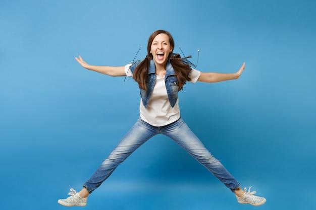 Полнометражный портрет молодой обрадованной студентки в джинсовой одежде, прыгающей, распространяя руки и ноги, кричащие на синем фоне. обучение в средней школе. скопируйте место для рекламы.