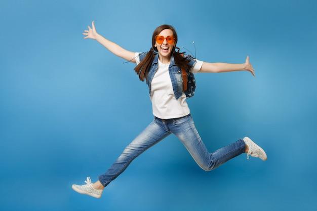Полнометражный портрет молодой обрадованной студентки с рюкзаком в оранжевых очках сердца прыгает, раздвигая руки, ноги, изолированные на синем фоне. обучение в средней школе. скопируйте место для рекламы.