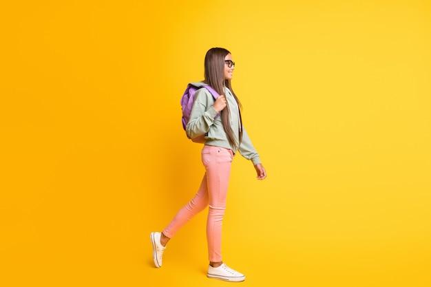 若い人の完全な長さの肖像画は、鮮やかな黄色の背景に分離されたバックパック着用パーカーを運ぶ