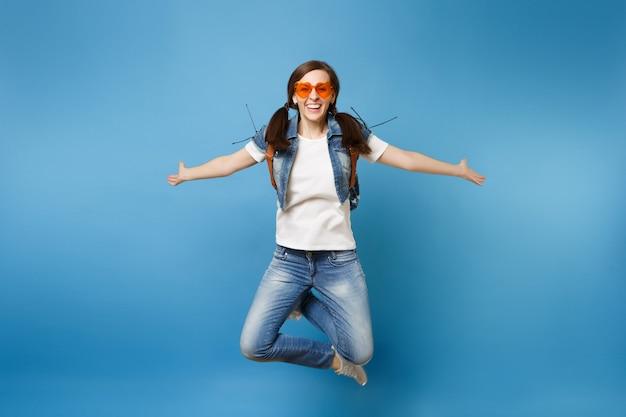 Полнометражный портрет молодой улыбающейся студентки в оранжевых очках сердца, прыгающих со скрещенными ногами, раздвигающими руки, изолированные на синем фоне. обучение в колледже. скопируйте место для рекламы.