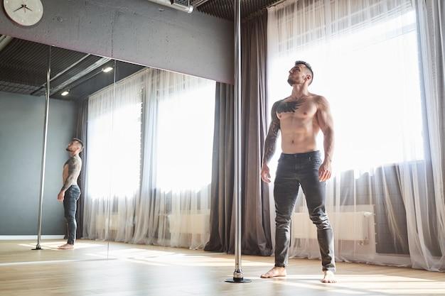 パイロンを見ている灰色のズボンの若い強いポールダンサーの男の全身像