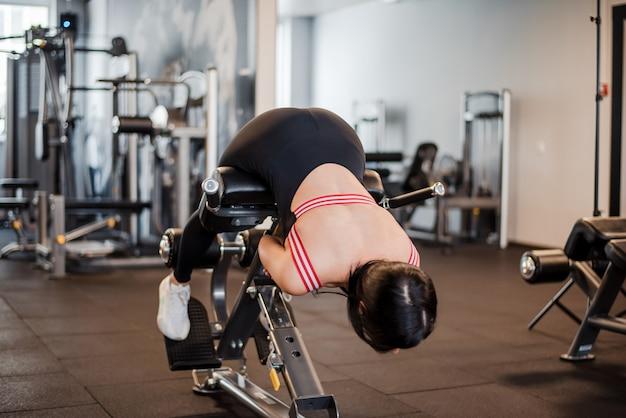 ジムで過伸展をしている若い女性の全身像。スリムな女性が背中を曲げ、腹筋をベンチに置き、見下ろします。スポーツの概念。