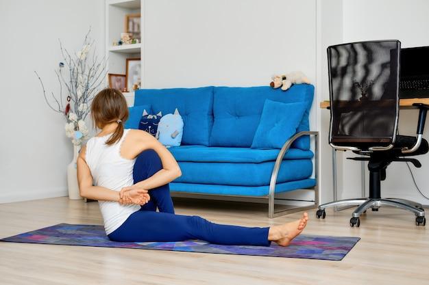 Полная длина портрет молодой женщины, делающей позу маричи йоги