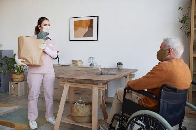 식료품이 든 가방을 들고 휠체어를 탄 노인에게 음식을 배달하는 젊은 여성의 전체 길이 초상화, 복사 공간