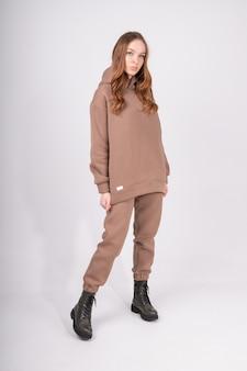 Портрет молодой женщины в серо-коричневой толстовке и стильных грубых сапогах в полный рост изолированы