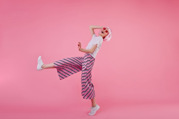 幸せな笑顔で踊る流行のパンツの若い女性の全身像。ピンクのかつらを楽しんでいるスリムでスタイリッシュな女の子の屋内ショット