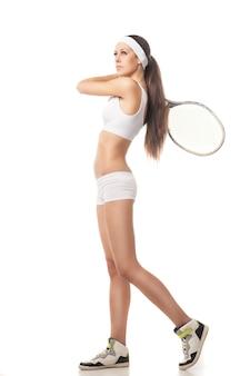 テニスをしている若い女性の全身像白い背景で隔離