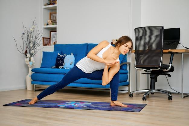Полный портрет молодой женщины, практикующей йогу дома, протягивая руку и ногу