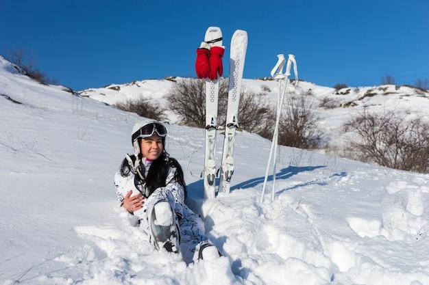 Портрет молодой женщины с длинными темными волосами в шлеме и очках в полный рост, сидящей в снегу на склоне горы с лыжами и палками рядом в солнечный день с голубым небом и теплым солнцем