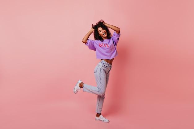 Ritratto integrale della donna che ride ottimista ballando in studio. modello femminile riccio rilassato che gode della vita.