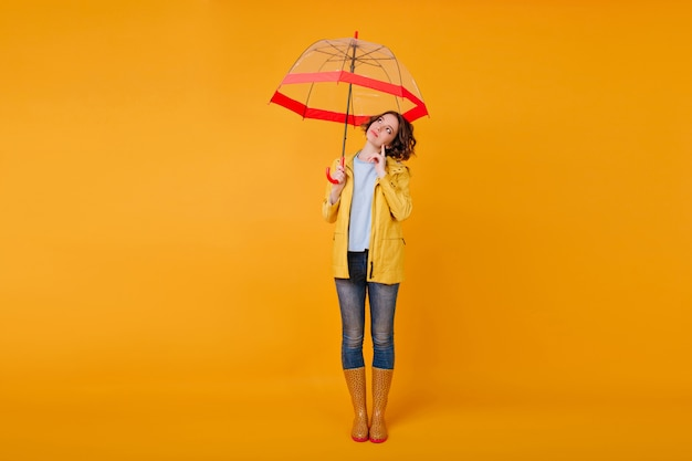 Full-length portrait of pensive romantic girl standing on yellow wall under red parasol. studio shot of stylish female model in jeans and autumn shoes looking away while posing with umbrella.