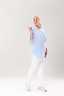 Full-length portrait of playful mature woman in blue shirt and white pants, standing and pointing with finger, looking aside