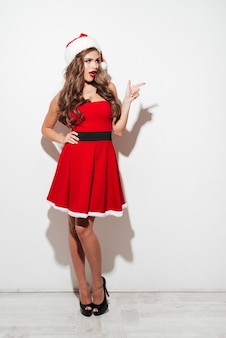 Full length portrait of a playful young brunette woman in red santa claus dress pointing finger away isolated over white surface