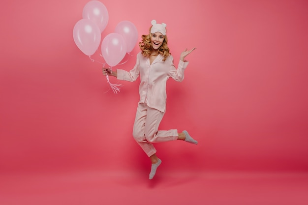 Full-length portrait of pleasant birthday girl in socks jumping on pink wall. cute young woman in pyjamas and sleepmask having fun with helium balloons.