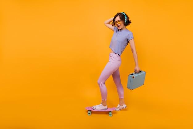 Ritratto integrale della ragazza positiva con la posa blu della valigia. modello femminile riccio giocondo in piedi sul longboard e sorridente.