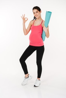 Full length portrait of pregnant fitness woman showing ok sign