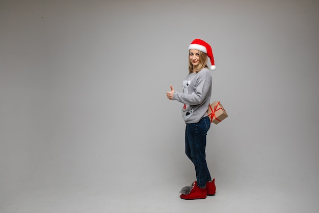 Full length portrait of pretty blonde woman in red santa hat, sweater, jeans and boots holding gift behind her back and showing thumb up in approval