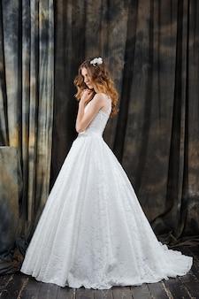 Full length portrait of pretty bride standing in profile