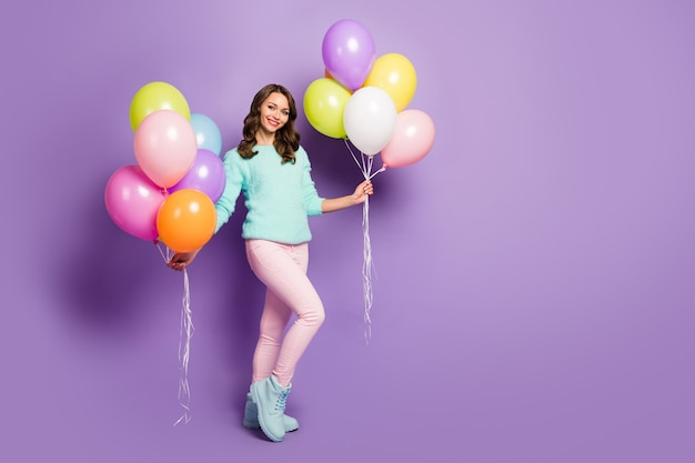 Full length portrait of pretty funny lady bring many colorful air balloons friends event birthday party wear fuzzy sweater pink pastel pants boots.