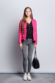 Full length portrait of pretty girl in down jacket and jeans standing near the wall with hand bag