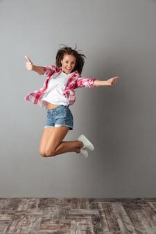 Ritratto integrale della bella donna che salta in abbigliamento casual, mostrando il pollice in su gesto
